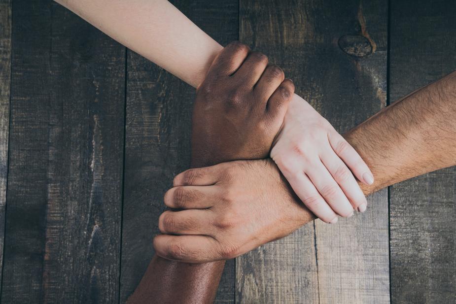 team hands linked together at omgloh.com